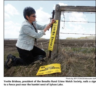 Yvette Brideau, president of the Benalto Rural Crime Watch Society, nails a sign to a fencepost near the hamlet west of Sylvan Lake Alberta.